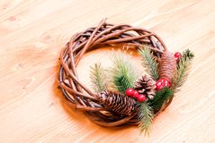 Christmas wreath of twigs with pine needles and cones on a yello Stock Photos