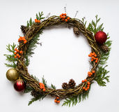 Christmas wreath of vines with decorative ornaments, thuja branches, rowanberries and cones. Flat lay, top view Stock Images