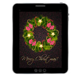 Christmas wreath on vintage background at tablet. Royalty Free Stock Photography