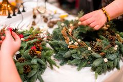 Christmas wreath weaving workshop. Woman hands decorating holida royalty free stock image