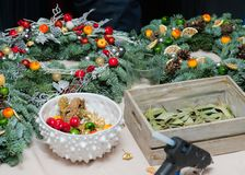 Christmas wreath weaving workshop. Woman hands decorating holiday wreath made of spruce branches, cones and various organic stock image