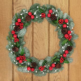 Christmas Wreath Welcome Symbol. Christmas wreath decoartion with red bauble decorations, holly, snow covered blue spruce fir and mistletoe over oak wood front Stock Photos