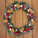 Christmas Wreath Welcome Symbol. Christmas wreath with dried fruit, candy canes, gold star and red baubles, holly, mistletoe, pine cones and snow covered blue Royalty Free Stock Photography