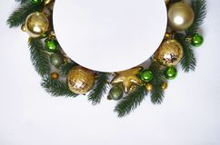 Christmas wreath on white background, banner with fir branches and balls. View from above. Colors are golden, green and white. New Royalty Free Stock Image