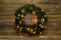 Christmas wreath with white lights on rustic wooden boards royalty free stock image