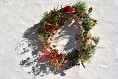 Christmas wreath with wild berries thorn berries and dog rose berries, pine with cones, dry flowers and leaves, white wall. Surface stock images
