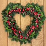 Christmas Wreath. Christmas and winter heart shaped wreath with holly, mistletoe, red bauble decorations and greenery over oak front door background Stock Photos