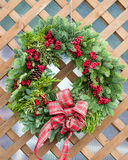 Christmas wreath on wood background. A Christmas wreath on lattice background stock image