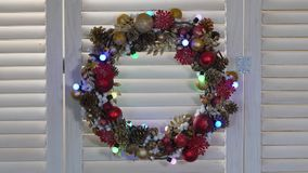 Christmas wreath on a wood background. With flashing garland stock video footage