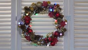 Christmas wreath on a wood background. With flashing garland, dolly shot stock video