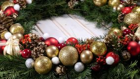 Christmas wreath on a wood background. Rotating detail of a christmas wreath on a wood background stock video footage