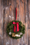 Christmas wreath on the wooden background. Christmas wreath with natural decorations hanging on a rustic wooden wall with Royalty Free Stock Image