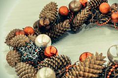 Christmas wreath on wooden board. Christmas wreath with red balls and cones on wooden board Stock Photography