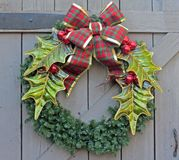 Christmas Wreath on a Wooden Door. A beautiful Christmas Wreath decorates a rustic Wooden Door for the Holiday Season stock photo