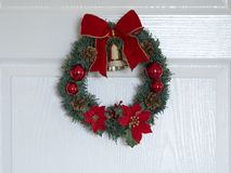 Christmas wreath on wooden door. Home decoration with ornaments royalty free stock image