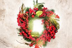 Christmas wreath on wooden door. Festive Christmas wreath on stone table. Holiday background. Toned image. Space for text stock images