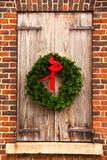 Christmas Wreath, Wooden Shutters, Red Brick Wall Stock Photo