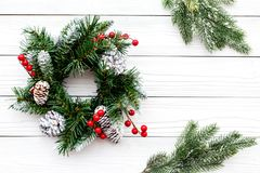 Christmas wreath woven of spruce branches with red berries on white wooden background top view copyspace Stock Photo