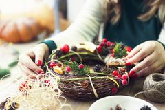 Christmas wreath in young womans hands. Christmas handmade wreath in young womans hands. Winter holidays celebration concept royalty free stock image