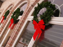 Christmas Wreathes. Hang on the windows of a beautiful brick home in the winter Royalty Free Stock Images