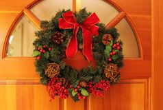 Christmas Wreaths. Christams wreaths hanging on a wooden entrance door Royalty Free Stock Images