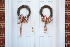 Christmas wreaths on doors. Christmas wreaths hanging on doors outside with red ribbon bows royalty free stock photo