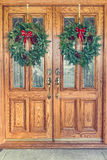 Christmas Wreaths on Front Doors. Two Christmas wreaths hanging from a double front door royalty free stock photography