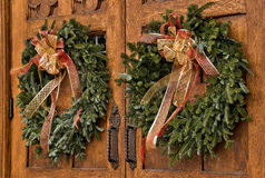 Christmas wreaths on wooden doors. A pair of festive Christmas evergreen wreaths adorn a set of large wooden doors, serving as decorations during the holiday royalty free stock images