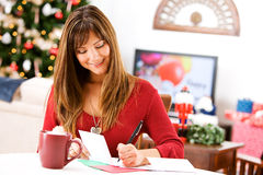 Christmas: Writing Holiday Cards at Table Royalty Free Stock Photography