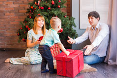 Christmas, x-mas, family, people, happiness concept - happy parents playing with cute baby boy Royalty Free Stock Photos