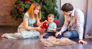 Christmas, x-mas, family, people, happiness concept - happy parents playing with cute baby boy Stock Photo
