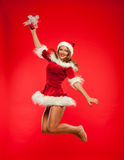 Christmas, x-mas, winter, concept - smiling woman in santa helper hat with gift box, happiness jump for joy over red Royalty Free Stock Photography