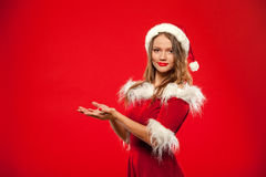 Christmas, x-mas, winter, happiness concept - smiling woman in santa helper hat with gift box, holding hands in front of Stock Photography