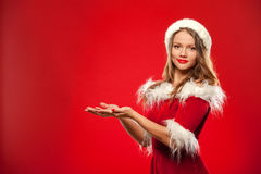 Christmas, x-mas, winter, happiness concept - smiling woman in santa helper hat with gift box, holding hands in front of Royalty Free Stock Images