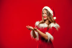 Christmas, x-mas, winter, happiness concept - smiling woman in santa helper hat with gift box, holding hands in front of Stock Images