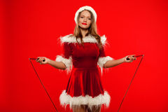 Christmas, x-mas, winter, happiness concept - Sport, activity. Cute woman with skipping rope in santa helper hat , over Royalty Free Stock Photos