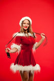 Christmas, x-mas, winter, happiness concept - Sport, activity. Cute woman with skipping rope in santa helper hat , over Royalty Free Stock Images