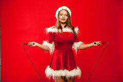 Christmas, x-mas, winter, happiness concept - Sport, activity. Cute woman with skipping rope in santa helper hat , over Stock Photo
