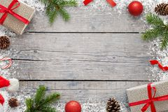 Christmas Xmas background with copy space for text. Christmas fir branches, giftse, lollipop, Santa hat, pinecones and snowflakes. On wooden table. Top view royalty free stock images