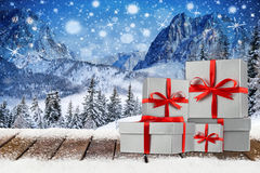 Christmas xmas background with red silver gift boxes. Christmas xmas background with red silver ribbon gift present boxes on wooden snowy planks in front of royalty free stock images