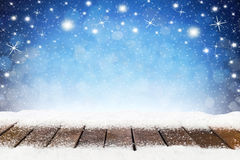 Christmas xmas background with wooden snowy planks. In front of blue night sky with stars and snowflakes Stock Photo