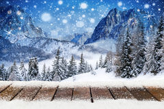 Christmas xmas background with wooden snowy planks. In front of mountain forest landscape blue night sky with stars and snowflakes stock photo