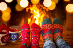 Christmas Xmas Family Holiday Winter. Family in Christmas socks near fireplace. Mother; father and baby having fun together. People relaxing at home. Winter Stock Images