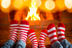 Christmas Xmas Family Holiday Winter. Family in Christmas socks near fireplace. Mother; father and baby having fun together. People relaxing at home. Winter stock image