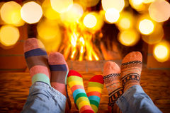 Christmas Xmas Family Holiday Winter. Family in Christmas socks near fireplace. Mother; father and baby having fun together. People relaxing at home. Winter Stock Photography