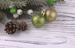 Christmas Xmas New Year holiday background with golden gift box green and gold balls natural fir branches cones on white wooden ba Royalty Free Stock Image