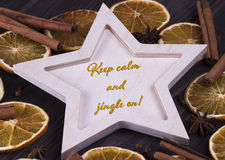 Christmas Xmas New Year Holiday card with wooden star cinnamone star anice dried oranges and text Keep calm and jingle on. Christmas Xmas New Year Holiday royalty free stock photos