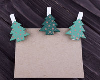 Christmas Xmas New Year Holiday greeting card concept with emty sheet of cardboard three Christmas tree on clothespins on dark woo. Den background, space for stock images