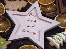Christmas Xmas New Year Holiday greeting card with wooden star cinnamone star anice dried oranges Christmas tree cookies and text Royalty Free Stock Photography