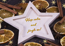 Christmas Xmas New Year Holiday greeting card with wooden star cinnamone star anice dried oranges snowflakes and text Keep calm an Stock Images
